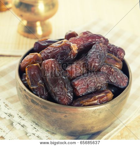 Dried date palm fruits or kurma, ramadan food which eaten in fasting month. Pile of fresh dried date fruits ready to eat in metal bowl.