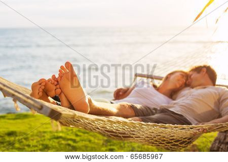 Romantic couple relaxing in tropical hammock at sunset, Shallow depth of field, focus on feet.
