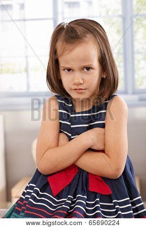 Little girl sitting arms crossed, sulking