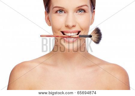 Smiling girl with powder brush in her teeth looking at camera over white background