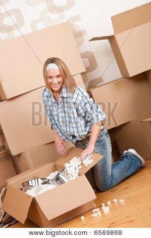 Mudanza: Mujer feliz desempacar la caja