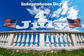 image of balustrade  - White stone balustrade with two US flags on blue sky with clouds and phrase  - JPG