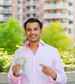 image of colombian currency  - Closeup portrait super happy excited successful young businessman pointing to money - JPG