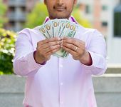 stock photo of colombian currency  - Closeup cropped portrait happy successful young businessman holding showing money - JPG