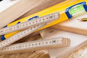 picture of joinery  - Close up view of a colorful yellow carpenters level ruler and right angle lying on planks of new hardwood together with a pencil for measurements in a carpentry construction DIY and joinery concept  - JPG