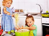 stock photo of pinafore  - Children  eating spaghetti at kitchen - JPG