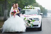 stock photo of limousine  - Happy bride and groom near wedding limo - JPG