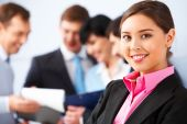 picture of young adult  - Photo of pretty business leader looking at camera in working environment - JPG