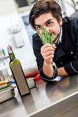 Постер, плакат: Chef Checking The Freshness Of A Bunch Of Herbs