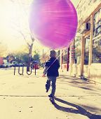 pic of instagram  - little boy running with a balloon done with a retro vintage instagram filter - JPG