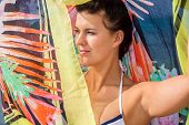 foto of vivacious  - Beautiful vivacious young woman wearing a bikini and holding a colorful scarf around her shoulders enjoying a hot summer day at the seaside giving the camera a lovely friendly smile ocean background - JPG