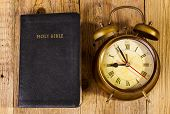 stock photo of time study  - Holly Bible with clock on wood - JPG