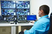 stock photo of security  - security guard watching video monitoring surveillance security system - JPG
