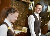 stock photo of front-entry  - Happy receptionist worker standing at hotel counter - JPG