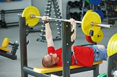 stock photo of triceps brachii  - athlete man at arm muscles exercises with training weight in fitness club gym - JPG