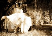 image of weeping willow tree  - Young bride having fun while sitting on a bench under a weeping willow tree - JPG