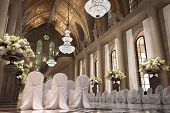 stock photo of wedding arch  - Church Cathedral wedding interior with rows of elegant chairs and flowing flower arrangements - JPG