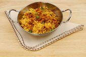 pic of biryani  - Lamb biryani in a balti dish with a serviette on a wooden table top - JPG