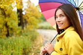 foto of girl walking away  - Woman happy with umbrella under the rain during Autumn forest walk - JPG