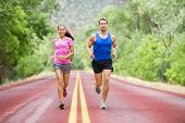 foto of multicultural  - Running young multicultural couple exercising fitness outside on road in pretty nature jogging happy smiling - JPG