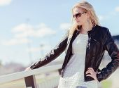 stock photo of jacket  - Fashionable beautiful young blond wearing a leather jacket warm sunny day - JPG
