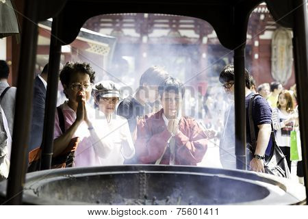 TOKYO, JAPAN - CIRCA MAY 2014: People pray at Senso-ji Temple in Tokyo,Japan. The Senso-ji Temple is the symbol of Asakusa and one of the most famed temples in Japan.