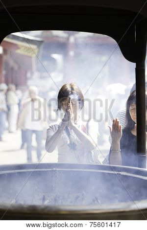 TOKYO, JAPAN - CIRCA MAY 2014: Tourists pray at Senso-ji Temple in Tokyo,Japan. The Senso-ji Temple is the symbol of Asakusa and one of the most famed temples in Japan.