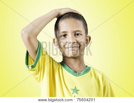 Brazilian little boy putting his hand on his head on yellow background