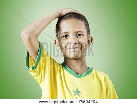 Brazilian little boy putting his hand on his head on green background