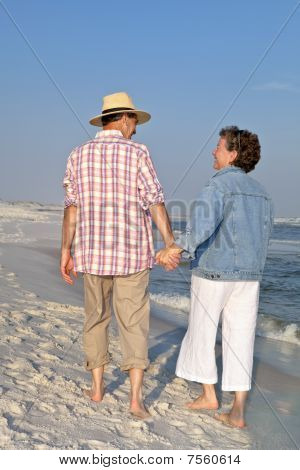 Happy Couple Strolling On Beach At Sunset