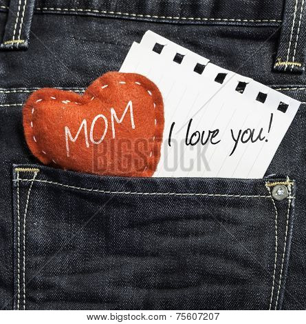 Mom I love you! written on a peace of paper and a heart on a jeans background