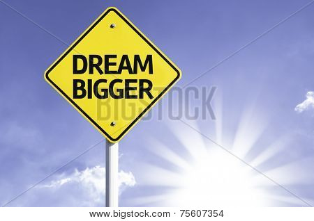 Dream Bigger road sign with sun background