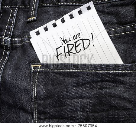 You are Fired! written on a peace of paper on a jeans background