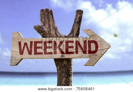 Weekend wooden sign with a beach on background