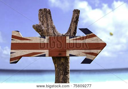 United Kingdom wooden sign with a beach on background