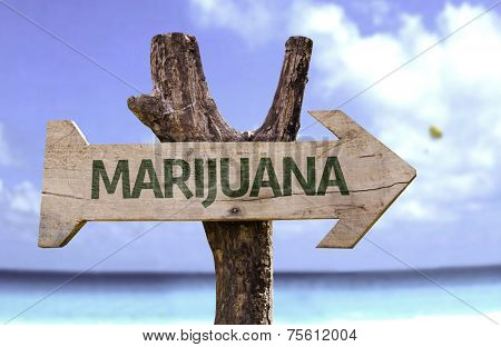Marijuana wooden sign with a beach on background