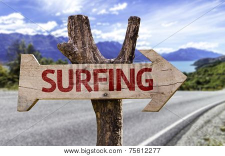 Surfing wooden sign with a street background
