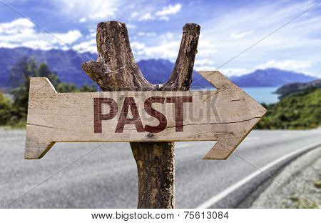 Past wooden sign with a street background