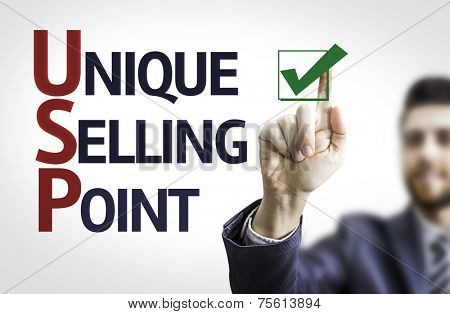 Business man pointing to transparent board with text: Unique Selling Point