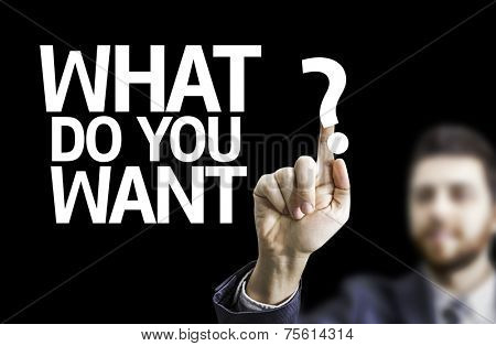 Business man pointing to black board with text: What Do You Want?