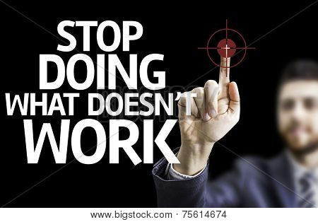 Business man pointing to black board with text: Stop Doing What Doesn't Work