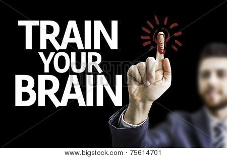 Business man pointing to black board with text: Train your Brain