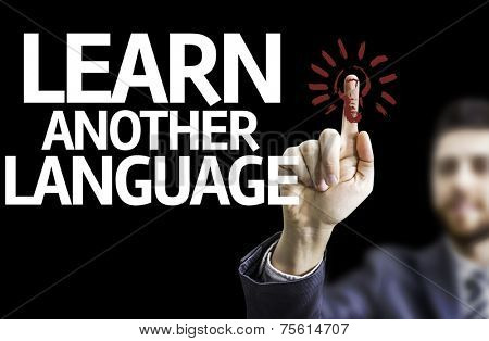 Business man pointing to black board with text: Learn Another Language