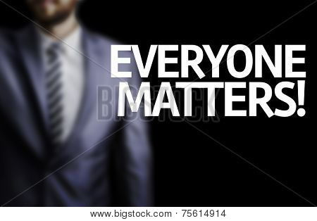 Everyone Matters written on a board with a business man on background