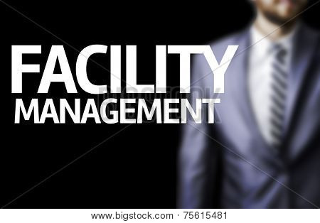 Facility Management written on a board with a business man on background