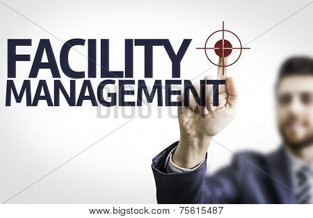 Business man pointing to transparent board with text: Facility Management