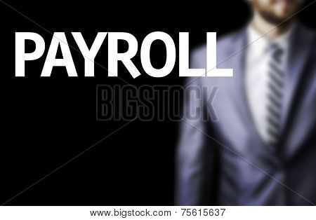 Payroll written on a board with a business man on background