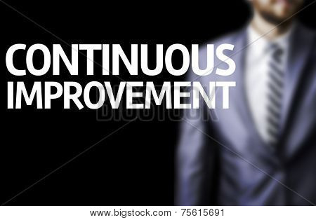 Continuous Improvement written on a board with a business man on background