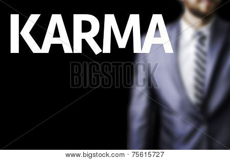 Karma written on a board with a business man on background