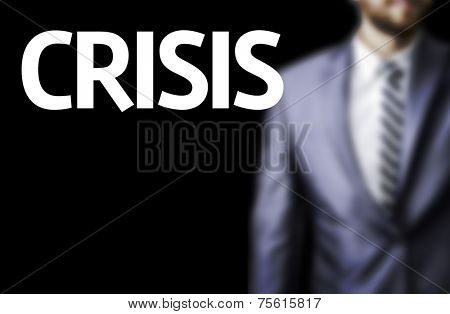 Crisis written on a board with a business man on background